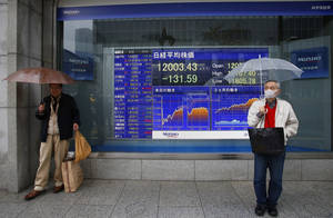 Photo - Men wait for a signal to change in front of an electronic stock indicator in Tokyo, Japan, Tuesday, April 2, 2013. A slowdown in U.S. factory production sent Asian stock markets lower Tuesday, while Japan's Nikkei slipped as the yen rose against the dollar. (AP Photo/Shizuo Kambayashi)