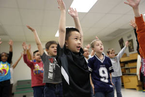 photo - Right: First-grader Brian Bui practices during Christy Gosset's music class for a musical program at  Western Oaks Elementary.