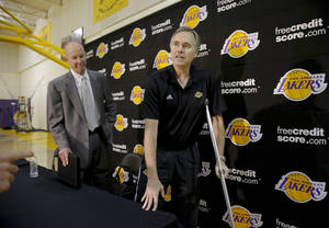 photo -   New Los Angeles Lakers coach Mike D'Antoni, right, is accompanied by vice president of public relations John Black as they leave after an NBA basketball news conference in El Segundo, Calif., Thursday, Nov. 15, 2012. Although D'Antoni is still on crutches after his recent knee surgery, he is already at work with the Lakers. (AP Photo/Jae C. Hong)