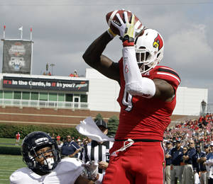 Photo - Louisville wide receiver DeVante Parker, right, grabs a touchdown pass over Florida International cornerback Sam Miller, left, in the first quarter of an NCAA college football game in Louisville, Ky., Saturday, Sept, 21, 2013.  (AP Photo/Garry Jones)