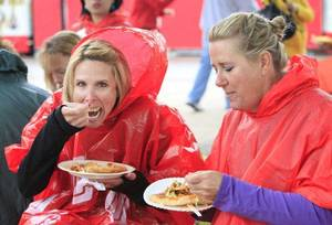 Photo - Kim Toney, from Norman, and Lisa Gordon, from Erick, eat Indian Tacos in their rain gear during the opening day of the 2011 Oklahoma State Fair, Thursday, September 15, 2011.    Photo by David McDaniel, The Oklahoman  ORG XMIT: KOD