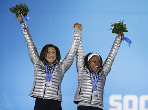 Photo - Women's bobsleigh silver medalists Elana Meyers, left, and Lauryn Williams of the United States celebrate during their medals ceremony at the 2014 Winter Olympics, Thursday, Feb. 20, 2014, in Sochi, Russia. (AP Photo/David Goldman)