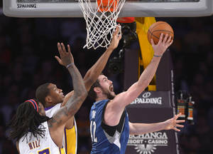 Photo - Minnesota Timberwolves forward Kevin Love, right, puts up a shot as Los Angeles Lakers center Jordan Hill, left, and guard Wesley Johnson defend during the first half of an NBA basketball game, Sunday, Nov. 10, 2013, in Los Angeles. (AP Photo/Mark J. Terrill)