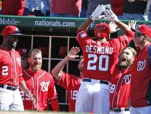 Photo - Washington Nationals' Ian Desmond (20) celebrates with Jayson Werth, second from right, and other teammates after hitting a game-winning solo home run during the seventh inning of a baseball game against the Atlanta Braves at Nationals Park, Sunday, April 6, 2014, in Washington. The Nationals won 2-1. (AP Photo/Alex Brandon)