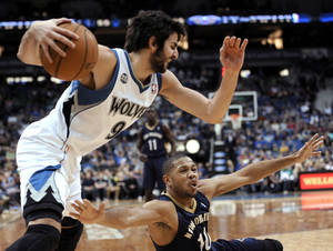 Photo - New Orleans Pelicans' Eric Gordon (10) reaches for the ball as Minnesota Timberwolves' Ricky Rubio (9) comes up with it during the second quarter of an NBA basketball game  Wednesday, Jan. 1, 2014, in Minneapolis. (AP Photo/Hannah Foslien)