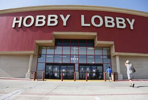 """Photo - FILE - This June 30, 2014, file photo shows customers walking into a Hobby Lobby store in Oklahoma City. There may be more to that """"we the people"""" notion than you thought.These are boom times for the concept of """"corporate personhood."""" Corporations are people? Mitt Romney got mocked during the 2012 presidential campaign for the very idea. But it turns out the principle has been lurking in U.S. law for more than a century, and the Supreme Court, in a 5-4 ruling, gave it more oomph this week when it ruled that certain businesses are entitled to exercise religious rights just as do people. (AP Photo/Sue Ogrocki, File)"""