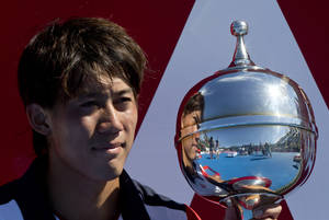 Photo - Japan's Kei Nishikori holds the trophy after win over Tomas Berdych of the Czech Republic in their final match of the Kooyong Classic ahead of the Australian Open tennis championship in Melbourne, Australia, Saturday, Jan. 11, 2014. (AP Photo/Joshua Baker)