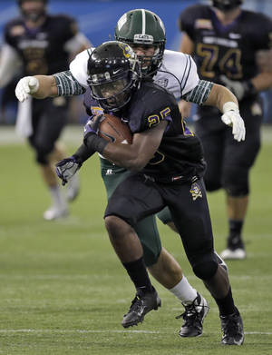 Photo - East Carolina running back Breon Allen (25) escapes the grasp of Ohio defensive end Kurt Laseak (99) during the first quarter of the Beef 'O' Brady's Bowl NCAA college football game Monday, Dec. 23, 2013, in St. Petersburg, Fla. (AP Photo/Chris O'Meara)