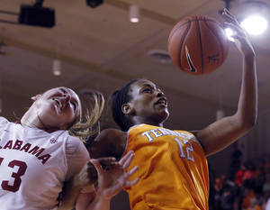 Photo - Tennessee's Bashaara Graves (12) pulls in a rebound over Alabama's Nikki Hegstetter (13) during the first half of an NCAA college basketball game, Sunday, Feb. 2, 2014, in Tuscaloosa, Ala. (AP Photo/Butch Dill)