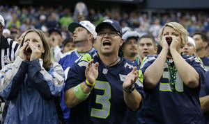 Photo - Seattle Seahawks fans yell during the first half of an NFL football game between the Seattle Seahawks and the San Francisco 49ers at CenturyLink Field, Sunday, Sept. 15, 2013, in Seattle. Fans were attempting to set a Guinness World Record for crowd noise at an athletic event during the game. (AP Photo/Elaine Thompson)
