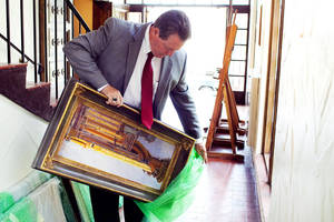 Photo -   Judge Fred Howard of Provo's 4th District Court unwraps one of his paintings as he delivers a collection of his work to the Springville Museum of Art on Friday, Aug. 31, 2012 in Springville, Utah. The museum is exhibiting 33 of Howard's paintings, which all depict the organ in the LDS Church's Salt Lake City Tabernacle. (AP Photo/Daily Herald, Spenser Heaps)