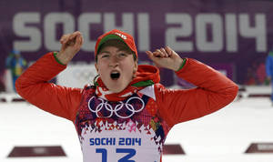 Photo - Belarus' Darya Domracheva celebrates winning the gold medal in the women's biathlon 15k individual race, at the 2014 Winter Olympics, Friday, Feb. 14, 2014, in Krasnaya Polyana, Russia. (AP Photo/Lee Jin-man)
