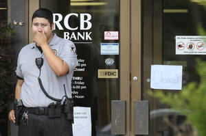 Photo -  An off-duty Oklahoma County sheriff's deputy stands at the front door to RCB Bank, 11217 N May Avenue, in Oklahoma City on Tuesday. The deputy struggled with a bank robber before the robber fled on foot. PHOTO BY STEVE GOOCH, THE OKLAHOMAN  <strong>Steve Gooch -   </strong>