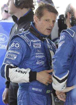 Photo - Oswaldo Negri Jr., of Brazil, talks with a crew member during practice for the Rolex 24 hour auto race at Daytona International Speedway, Thursday, Jan. 24, 2013, in Daytona Beach, Fla. (AP Photo/John Raoux)