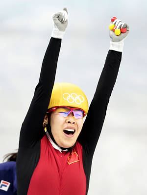 Photo - Zhou Yang of China celebrates as she crosses the finish line first in a women's 1500m short track speedskating final at the Iceberg Skating Palace during the 2014 Winter Olympics, Saturday, Feb. 15, 2014, in Sochi, Russia. (AP Photo/Ivan Sekretarev)