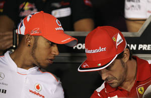 Photo -   Ferrari driver Fernando Alonso, right, of Spain, talks with McLaren Mercedes driver Lewis Hamilton, of Britain, during a press conference at the Monza Formula One circuit, in Monza, Italy, Thursday, Sept. 6, 2012. The Formula One race will be held on Sunday. (AP Photo/Antonio Calanni)