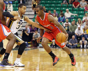 Photo - Los Angeles Clippers' Chris Paul, right, dribbles past Utah Jazz's Trey Burke in the first quarter during an NBA preseason basketball game on Saturday, Oct. 12, 2013, in Salt Lake City. (AP Photo/Kim Raff)