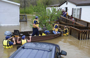 Photo - CORRECTS DATE TO APRIL 7 Firefighters rescue a family from their home, surrounded by floodwaters, in a mobile home park in Pelham, Ala., on Monday, April 7, 2014. Overnight storms dumped torrential rains in central Alabama, causing flooding across a wide area. (AP Photo/Jay Reeves)