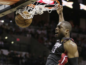 Photo - Miami Heat's Dwyane Wade (3) dunks against the San Antonio Spurs during the second half at Game 4 of the NBA Finals basketball series, Thursday, June 13, 2013, in San Antonio. (AP Photo/Eric Gay)