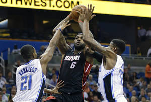 Photo - Miami Heat's LeBron James (6) makes a shot as he is guarded by Orlando Magic's Maurice Harkless (21) and Solomon Jones, right, during the first half of an NBA basketball game in Orlando, Fla., Wednesday, Nov. 20, 2013. (AP Photo/John Raoux)