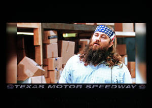 "Photo - Fans were able to watch tonight's episode of Duck Dynasty on Big Hoss, one of the stars, Willie Robertson on screen here, and his wife were in attendance at TMS. Texas Motor Speedway debuted their new Big Hoss TV screen, a 218 x 94 foot screen over the east grandstands of the racetrack, Wednesday, March 19, 2014. The first show to be seen on the screen by the public is Wednesday's episode of ""Duck Dynasty"", sponsors of the upcoming April NASCAR race, the Duck Commander 500. (AP Photo/The Fort Worth Star-Telegram, Paul Moseley)"