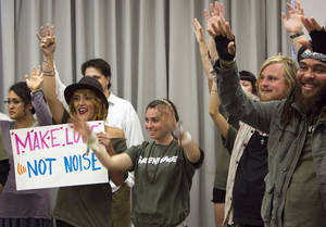 Photo -   Environmentalists and supporters of Greenpeace hold their hands up to express their support for fellow speakers during a California Coastal Commission meeting in Santa Monica, Calif. Wednesday, Nov. 14, 2012. The California Coastal Commission is weighing whether to grant a permit to the Pacific Gas & Electric Co. to conduct seismic imaging off the coast of the Diablo Canyon nuclear plant. (AP Photo/Damian Dovarganes)