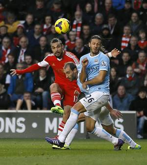 Photo - Southampton's Pablo Daniel Osvaldo, left, scores a goal past  Manchester City's Martin Demichelis during the English Premier League soccer match between Southampton and Manchester City at St Mary's Stadium in Southampton, England Saturday, Dec. 7, 2013. (AP Photo/Kirsty Wigglesworth)