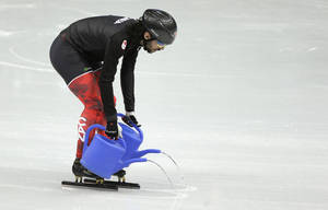 Photo - Canadian short track speed skating team member Charles Hamelin pours water on the ice during a training session at the Iceberg Skating Palace ahead of the 2014 Winter Olympics, Tuesday, Feb. 4, 2014, in Sochi, Russia. (AP Photo/Mark Baker)