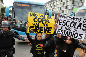 "Photo - Demonstrators hold up signs that read in Portuguese ""There won't be a Cup. There will be strikes,"" center, and ""We need schools, not stadiums"" as they walk in front of the bus carrying members of Brazil's national soccer team as it leaves a hotel for the Granja Comary training center, where the team will train and reside during the World Cup, in Rio de Janeiro, Brazil, Monday, May 26, 2014. Demonstrators are protesting the money being spent by the local government on the World Cup. (AP Photo/Leo Correa)"