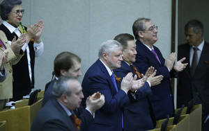 Photo - Members of the State Duma, lower parliament chamber, applaud for their voting during a plenary session in Moscow, Russia, Thursday, March 20, 2014.  The Kremlin-controlled State Duma voted Thursday to allow Crimea to join Russia following a quick discussion in which members of the Kremlin-controlled chamber assailed the Ukrainian authorities. The merger needs to be rubber stamped by the upper house and signed by President Vladimir Putin, mere formalities expected to be completed by the end of the week.   (AP Photo/Alexander Zemlianichenko)