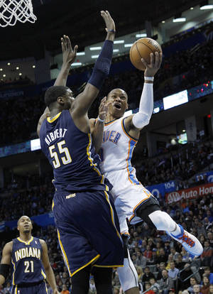 photo - Oklahoma City Thunder guard Russell Westbrook (0) shoots in front of Indiana Pacers center Roy Hibbert (55) in the first quarter of an NBA basketball game in Oklahoma City, Sunday, Dec. 9, 2012. (AP Photo/Sue Ogrocki)