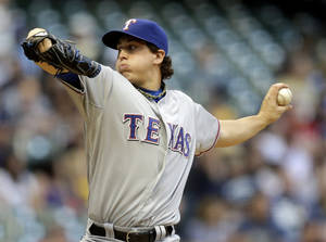 Photo - Texas Rangers starting pitcher Derek Holland throws during the first inning of a baseball game against the Milwaukee Brewers Wednesday, May 8, 2013, in Milwaukee. (AP Photo/Morry Gash)