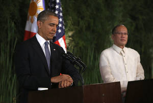 Photo - U.S. President Barack Obama looks at his watch before answering a reporter's question during a joint news conference with Philippines President Benigno Aquino III at Malacanang Palace in Manila, the Philippines, Monday, April 28, 2014. President Obama said a 10-year agreement signed Monday to give the U.S military greater access to Philippine bases will help promote regional security, improve armed forces training and shorten response times to humanitarian crises, including natural disasters. (AP Photo/Charles Dharapak)
