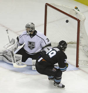 Photo - San Jose Sharks' Logan Couture, right, scores a goal against Los Angeles Kings' Jonathan Quick during the third period of Game 2 of an NHL hockey first-round playoff series Sunday, April 20, 2014, in San Jose, Calif. (AP Photo/Ben Margot)