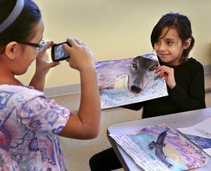 Photo - Cameron Samson (cq), 8, takes a picture of her friend, Candy Lopez, 9, holding the collage she made  during a workshop at the National Cowboy & Western Heritage Museum on Saturday morning, Nov. 3, 2012. Both girls live in Oklahoma City and both made artwork. Samson  used an owl as the centerpiece of her collage; Lopez collage's focus is a wolf.   The children, along with parents and grandparents who attended,  were given a variety of materials and asked to create a collage that rillustrated the resilient Spirit of the West, which was the theme of the workshop.   Photo by Jim Beckel, The Oklahoman