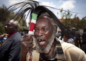 Photo -   Lawrence Mathenge, representative of the Mau Mau War Veterans Association, celebrates the announcement of a legal decision in Britain's High Court concerning Mau Mau veterans, while holding a ceremonial whisk, at the offices of the Kenya Human Rights Commission in Nairobi, Kenya Friday, Oct. 5, 2012. Britain's High Court ruled Friday that three Kenyans tortured during the Mau Mau rebellion against British colonial rule can proceed with compensation claims against the British government. (AP Photo/Ben Curtis)