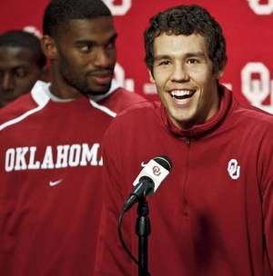Photo - Surrounded by his teammates,  Sam  Bradford addresses the media as he makes an official announcement that he is having season ending shoulder surgery, and plans to enter the NFL draft on Monday, Oct. 26, 2009, in Norman, Okla. (AP Photo/The Oklahoman, Chris Landsberger)