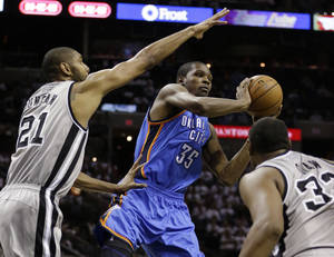 Photo - Oklahoma Thunder's Kevin Durant (35) looks to pass the ball as San Antonio Spurs' Tim Duncan (21) and Boris Diaw, right, of France, defend during the third quarter of an NBA basketball game, Thursday, Nov. 1, 2012, in San Antonio. (AP Photo/Eric Gay) ORG XMIT: TXEG111