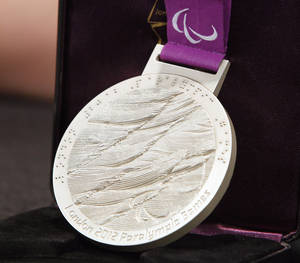 photo - Monique Burkland paralympic silver medal  at a press conference at Children's Hospital, Tuesday, November 27, 2012. Burkland had her leg amputated after a forklift accident and Ertl helped her with her recovery.  Photo By David McDaniel/The Oklahoman
