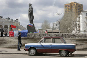 Photo - A man passes by the car painted in the colors of Russian flag near a Soviet-era monument to Vladimir Lenin in the central square in Donetsk, Ukraine, Tuesday, April 15, 2014.  Several government buildings have fallen to mobs of pro-Moscow loyalists in recent days as unrest spreads across the east of the country. (AP Photo/Efrem Lukatsky)