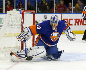 photo - New York Islanders goalie Evgeni Nabokov (20) makes a save in the first period of an NHL hockey game against the Montreal Canadiens at the Nassau Coliseum in Uniondale, N.Y., Tuesday, March 5, 2013. (AP Photo/Paul J. Bereswill)