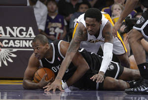 Photo - Brooklyn Nets center Jason Collins, left, battles for a loose ball with Los Angeles Lakers guard MarShon Brooks during the first half of an NBA basketball game, Sunday, Feb. 23, 2014, in Los Angeles. (AP Photo/Mark J. Terrill)