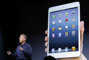 Photo -   Phil Schiller, Apple's senior vice president of worldwide product marketing, talks in front of a projection of the iPad mini in San Jose, Calif., Tuesday, Oct. 23, 2012. Apple Inc. is refusing to compete on price with its rivals in the tablet market it's pricing its new, smaller iPad well above the competition. On Tuesday, the company revealed the iPad Mini, with a screen that's about two-thirds the size of the full-size model, and said it will cost $329 and up. (AP Photo/Marcio Jose Sanchez)