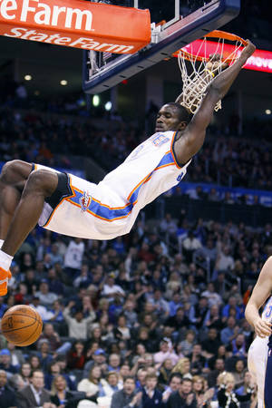 Photo - Oklahoma City's Serge Ibaka swings from the rim after dunking during the Thunder - Grizzlies game Saturday, January 8, 2011 at the Oklahoma City Arena. OKLAHOMAN ARCHIVE PHOTO