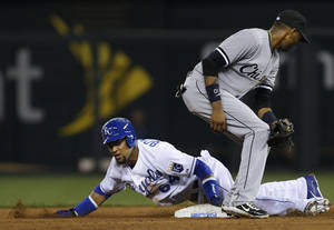 Photo - Kansas City Royals' Emilio Bonifacio (64) beats the tag by Chicago White Sox shortstop Alexei Ramirez, right, while stealing second base during the fifth inning of a baseball game at Kauffman Stadium in Kansas City, Mo., Thursday, Aug. 22, 2013. (AP Photo/Orlin Wagner)