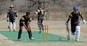 Photo -  Batsman Rey Ganadeep, at right, runs as bowler Jagan Patlolla waits for the ball March 29 during the Oklahoma City Strikers Cricket Club's first game on its new field at Douglass Park in Oklahoma City. Photo by Bryan Terry, the Oklahoman  <strong>Bryan Terry -   </strong>