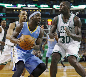 Photo - Denver Nuggets' Ty Lawson, center, drives for the basket as Boston Celtics' Brandon Bass (30) defends in the second quarter of an NBA basketball game in Boston, Friday, Dec. 6, 2013. (AP Photo/Michael Dwyer)