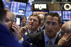 Photo - Traders gather at a post on the floor of the New York Stock Exchange, Tuesday, Aug. 27, 2013. Stocks declined broadly in early Tuesday trading as investors feared that the possibility of a U.S. military intervention in Syria could become a reality.  (AP Photo/Richard Drew)