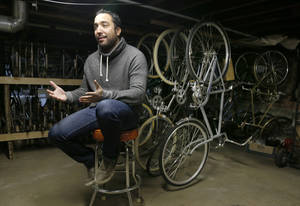 "Photo - In this photo taken Tuesday, Dec. 17, 2013, in Chicago, Mike Salvatore, owner of Heritage Bicycles talks about the emerging increase in bike riders at his Lakeview neighborhood store. A recent debate on a proposed city bicycle tax has put the spotlight back on cycling. Salvatore believes that no one would have taken that proposal seriously 10 years ago. ""Why would you tax bikers, who bikes?! Seriously, 10 years ago there was a handful of nutcases who biked around Chicago. No one would have taken it seriously."" (AP Photo/Charles Rex Arbogast)"