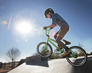 Photo - Enjoying a warm, sunny Wednesday, Blake Bella, 10, rides the bicycle he got for Christmas at Mitch Park in Edmond. Photo by David McDaniel, The Oklahoman